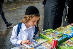 Rosh Hashanah, jüdisches neues Jahr 5777 Festlicher Straßenhandel Ein Hasid-Kind mit langen payos wählt ein Buch stockbild