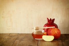 Rosh hashanah (jewesh holiday) concept - honey and pomegranate over wooden table. traditional holiday symbols. Royalty Free Stock Photo