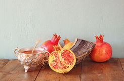 Rosh hashanah (jewesh holiday) concept - shofar, honey, apple and pomegranate over wooden table. traditional holiday symbols. Royalty Free Stock Photo