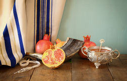 Rosh hashanah (jewesh holiday) concept - shofar, honey, apple and pomegranate over wooden table. traditional holiday symbols. Stock Photo