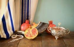 Rosh hashanah (jewesh holiday) concept - shofar, honey, apple and pomegranate over wooden table. traditional holiday symbols. Stock Photo