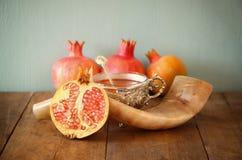 Rosh hashanah (jewesh holiday) concept - shofar, honey, apple and pomegranate over wooden table. traditional holiday symbols. Stock Photos