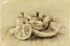 Rosh hashanah (jewesh holiday) concept - shofar, honey, apple and pomegranate over wooden table. traditional holiday symbols. blac Royalty Free Stock Image