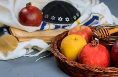 Rosh hashanah jewesh holiday concept - shofar, torah book, honey, apple and pomegranate over wooden table. a kippah a yamolka. Rosh hashanah jewesh holiday stock image