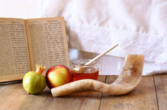 Rosh hashanah (jewesh holiday) concept - shofar, torah book, honey, apple and pomegranate over wooden table. traditional holiday s Royalty Free Stock Photography