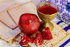Rosh hashanah jewish holiday matzoh passover bread Pomegranate. Pomegranate and glass of red wine close-up on mat Stock Photography
