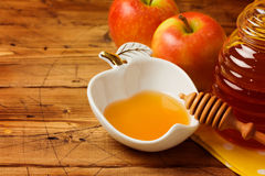 Rosh hashanah Jewish new year holiday celebration concept. Honey and apples. Over wooden background royalty free stock photo
