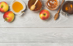 Rosh hashanah Jewish new year holiday celebration concept. Honey and apples over wooden background. Top view stock photos