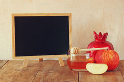 Rosh hashanah pojęcie blackboard, miód i granatowiec nad drewnianym stołem -, (jewesh wakacje) tradycyjni wakacyjni symbole obraz stock
