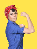 Rosie the Riveter. Classic World War II poster featuring Rosie the Riveter flexing her arm muscles against a yellow background. Includes clipping path Stock Photography