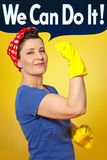 Rosie riveter cleaning gloves cloth. Cheerful woman cleaner with red kerchief, yellow cleaning gloves and cloth, holding up her arm and showing her muscles Royalty Free Stock Images