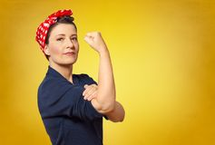 Rosie riveter woman copy space. Self-confident middle aged woman with a clenched fist rolling up her sleeve, text space, tribute to american icon Rosie Riveter Royalty Free Stock Images