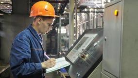 ROSJA, ANGARSK - CZERWIEC 8, 2018: Operator monitoruje pulpit operatora linia produkcyjna Manufaktura plastikowe wodne drymby zdjęcia stock