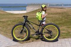 Rosja Bolgar, Czerwiec, - 09, 2019 Kol Gala kurortu zdrój: Dziecko dziewczyna z bicyklem GTX z plecakiem w jej ręka stojakach na  obrazy stock