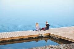 Rosja, Don 03 Czerwiec 2018 Dwa dziewczyny siedzi na moscie blisko dużego jeziora Zdjęcia Royalty Free