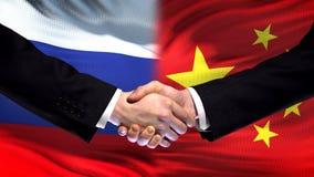Rosja i Chiny uścisk dłoni, międzynarodowy przyjaźń szczyt, chorągwiany tło zdjęcie royalty free