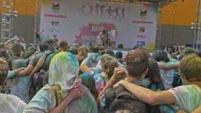 ROSJA IRKUTSK, CZERWIEC, - 27, 2018: Szczęśliwi młodzi ludzie tanczy i świętuje podczas Holi festiwalu kolory Tłum zdjęcie wideo