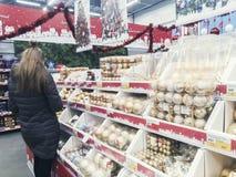 Rosja, listopad 10, 2018: ludzie wybierają Bożenarodzeniowe zabawki dla choinki w supermarkecie zdjęcia royalty free