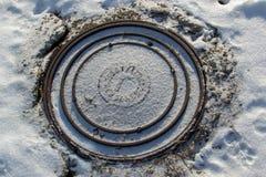 ROSJA, LUTY -, 2018: Ściekowy manhole na drodze w zimie obraz royalty free