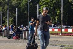 Rosja, Moskwa, 27 2018 Czerwiec, mężczyzna z walizką i telefon, artykuł wstępny Obraz Stock