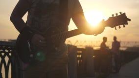 Rosja, Novosibirsk, 27 Lipiec, 2017 Zakończenie up mężczyzna ` s ręki bawić się gitarę przy zadziwiającym zmierzchem z obiektywu  Zdjęcie Royalty Free