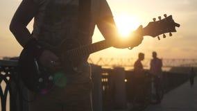 Rosja, Novosibirsk, 27 Lipiec, 2017 Zakończenie up mężczyzna ` s ręki bawić się gitarę przy zadziwiającym zmierzchem z obiektywu  Fotografia Stock