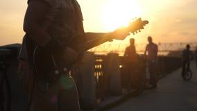 Rosja, Novosibirsk, 27 Lipiec, 2017 Zamyka up młody caucasian mężczyzna stoi outdoors w deptaku i bawić się gitarę przy Fotografia Stock