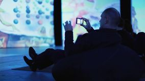 Rosja, Novosibirsk, 13 2015 Listopad Sztuki wystawa Dal Undefinded mężczyzna bierze obrazek od jego smartphone zdjęcie wideo