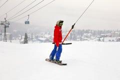 Rosja, Sheregesh 2018 11 18 Snowboarder w fachowym stroju wspina si? w g?r? narciarskiego podnosz? w g?r? g?ry E obraz stock