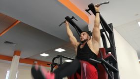 ROSJA, TOGLIATTY - LUTY 23, 2019: Sportowy mężczyzna trenuje mięśnie podbrzusze, wiesza na barze w gym zbiory wideo