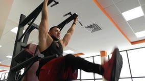 ROSJA, TOGLIATTY - LUTY 23, 2019: Sportowy mężczyzna trenuje mięśnie podbrzusze, wiesza na barze w gym zdjęcie wideo