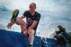 ROSJA, TOMSK, 1 2018 LIPIEC - mężczyzna pokonuje wodną przeszkodę na przeszkoda kursie Eestrremal sporty Czynnościowy szkolenie obrazy royalty free