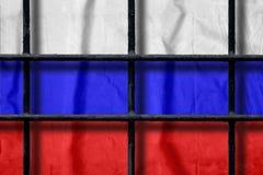Rosjanin flaga za czarnymi metalu więzienia barami z cieniami obrazy stock