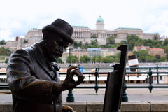 Roskovics Ignac statue in Budapest. Statue of Roskovics Ignac, a famous hungarian painter, on the sidewalk along the Danube in Budapest, Hungary. Buda castle on royalty free stock photos