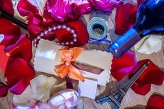 Roskronblad, pengar, flaskor av vin, en ask av juvlar och Eiffeltorn Arkivfoton