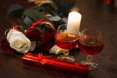 Rosor, exponeringsglas av vin och en ask med en juvel i ljuset av stearinljus Arkivfoton