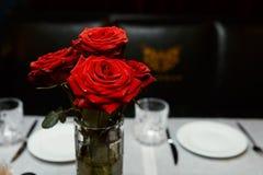 Rosor i en vas på en tabell Arkivbild