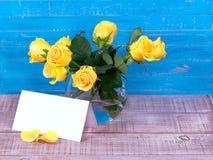 Rosor i en vas på träbakgrund och en vykort för text Royaltyfri Fotografi