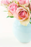 Rosor i ett ljus - blå vas på kräm- beige sjaskig chic bakgrund royaltyfri foto
