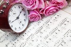 Rosor, klocka och musik arkivfoto