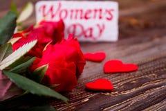 Rosor near kortet för dagen för kvinna` s Royaltyfria Foton