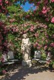 Rosor och gudstatyn i rosen arbeta i trädgården Beutig i Baden-Baden Royaltyfria Bilder