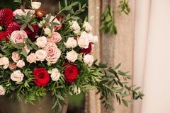Rosor och peons i vas på tabellnärbild arkivfoton