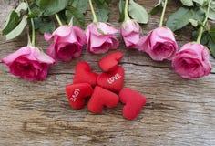 Rosor och röd hjärta kudde på det gamla träbrädet, valentindag b royaltyfri fotografi