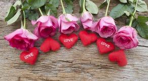 Rosor och röd hjärta kudde på det gamla träbrädet, valentindag b royaltyfri bild
