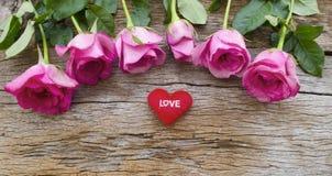 Rosor och röd hjärta kudde på det gamla träbrädet, valentindag b arkivfoto