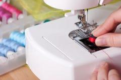 Rosqueando uma agulha na máquina de costura imagem de stock