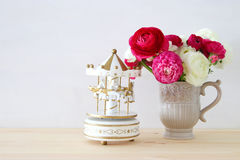 Rosses in the vintage vase and carousel horses. Bouquet of pink and white rosses in the vintage vase and carousel horses toy on wooden table Royalty Free Stock Photos