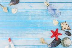 Rossetto della bottiglia di Parfume delle decorazioni delle conchiglie e stella di mare sopra Fotografie Stock Libere da Diritti