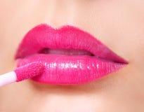 Rossetto di rosa caldo. Lucentezza del labbro sulle labbra e sulla spazzola sexy Fotografia Stock
